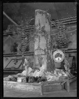 Pat Graham holds oranges and stands with a foot up on the Crest Forest Resort display at the National Orange Show, San Bernardino, 1934