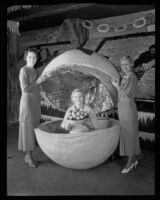 Lois Burr and Pat Graham hold the top of a giant orange in which May Betteridge, Queen of the National Orange Show, sits, San Bernardino, 1934