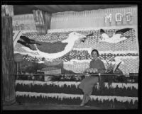 Woman sits on the Mutual Orange Distributors' display at the National Orange Show, San Bernardino, 1934