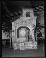 Woman stands upon the Great Orange County Association display at the National Orange Show, San Bernardino, 1934