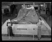 Two women stand in front of Cucamonga's display at the National Orange Show, San Bernardino, 1934