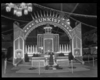 Woman stands in front of the Sunkist display at the National Orange Show, San Bernardino, 1934