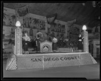 Four women pose on the San Diego County display at the National Orange Show, San Bernardino, 1933