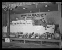 Woman sits upon the San Joaquin County display at the National Orange Show, San Bernardino, 1933