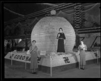 Margaret Garcia, Lucy Bennett, and an unnamed woman and the Corona display at the National Orange Show, San Bernardino, 1934
