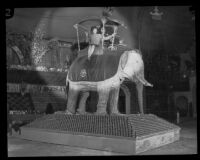 Woman sits atop an elephant-shaped display at the National Orange Show, San Bernardino, 1926