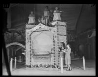 Woman stands next to a display at the National Orange Show, San Bernardino, 1926