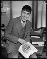 Japanese humorist Shiro Otsuji poses with a book or magazine, Los Angeles, 1935