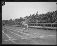 Charley Paddock leaping through finish line in USC shirt, Los Angeles, 1920s
