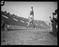 Charley Paddock leaping through finish line at Los Angeles Coliseum, 1920s