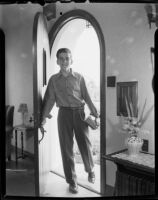 Young man with books coming through doorway, Santa Monica, [1940s?]