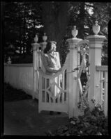Young woman at gate in garden, [1940s?]