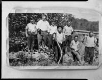 Men and boys with log and scythe, [1920s?, rephotographed 1940s?]