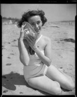Betty Herrick [?] on beach with seashell, 1953-1964