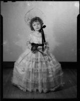 Helena Burnett in dress and bonnet holding a toy flower, Santa Monica, 1947-1950