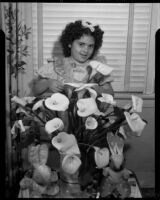 Barbara Lee Tramutto standing behind a vase of lillies, 1940-1945