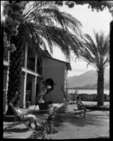 Ann Pruden and Mary Conners in outdoor area with palm trees, Palm Springs, 1940