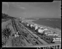 Young woman seated at the cliff edge in Palisades Park with PCH and Santa Monica Beach below, 1938-1950