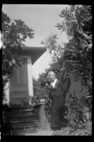 Woman standing next to the back door of a house