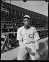 Baseball pitcher Satchel Paige seated next to bleachers, Los Angeles, circa 1933