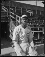 Baseball pitcher Satchel Paige seated next to bleachers, Los Angeles, circa 1933