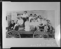 Group portrait of Will Rogers seated in a wagon with a group of men and women, circa 1900-1915