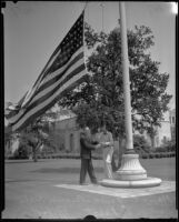Edward E. Spence and Norman A. Pabst fly the flag at half mast at City Hall upon news of the death of Will Rogers, Beverly Hills, 1935