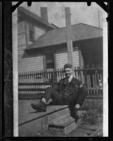 Actor Clark Gable as a young man, on porch with ukulele, [Ohio], [1920s?]