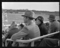 Actor Clark Gable and Ria Langham Gable in audience at outdoor event, 1930s