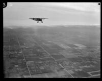 Aerial view of fields, streets, mountains, and airplane, Los Angeles, [1930s?]