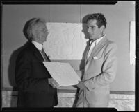 Sculptor Roger Burnham Noble and another man holding a relief panel, circa 1935-1939