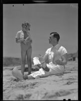 Actor Neil Hamilton and daughter Patricia on beach holding wooden shoes, Malibu, 1937