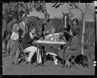 Actress Elissa Landi, family members, and friends having breakfast outdoors with horses and dog, [Los Angeles?], 1936