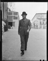 Man walking along street, 1927 or 1937