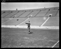 Football player Red Grange throwing football, Los Angeles Coliseum, Los Angeles, 1926