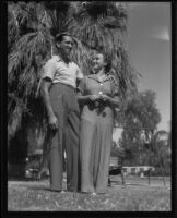 Defendant Roy Randolph and woman outdoors near palm tree, 1937
