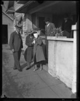 Kidnap victim Mary B. Skeele, blindfolded with detectives, outside the bungalow house where she was held, Pasadena, 1933