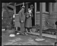 Kidnap victim Mary B. Skeele with detectives, blindfolded, at the bungalow house where she was held, Pasadena, 1933