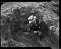 Man inspecting cracker box in hole, ransom drop-off point in Mary B. Skeele kidnap case, Los Angeles, 1933