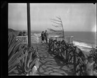 Woman and man standing near metal fence, Palisades Park, Santa Monica, [1930s?]