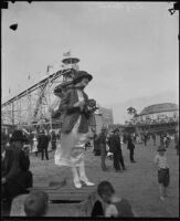 Woman with camera at amusement park, Long Beach, [1930s]