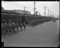 California National Guard members walking alongside train on Exposition Boulevard, Los Angeles, circa 1928-1939