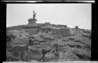 Man at top of rock formations at Red Rock Canyon State Park, California, circa 1920-1930