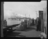 Naval officers on a pier with a view of ships probably at the Naval Station, San Diego, 1922-1939