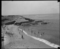 Sunbathers at a cliff-side beach, San Diego vicinity, 1920-1930