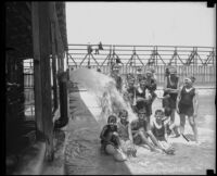 Children in bathing suits enjoying water spurting from an open pipe near a beach, San Diego vicinity, 1920-1930