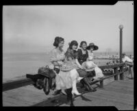 Four ladies seated on a pier railing, San Diego vicinity, 1920-1930