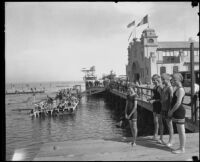 Sunbathers at a pier with a dance hall, swim platform and diving platform, San Diego vicinity, 1920-1930