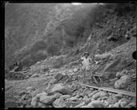 Gold miner M.L. Sims with wheelbarrow and shovel, San Gabriel Canyon, 1932