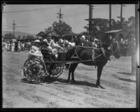 Three children in a pony-drawn cart during the Old Spanish Days Fiesta, Santa Barbara, 1932